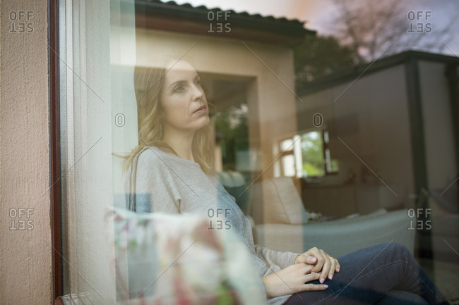 Thoughtful woman sitting by window seen through glass