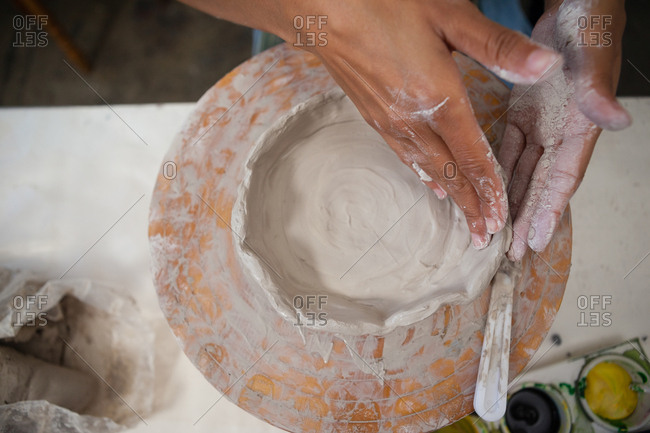 Close-up of potter molding clay in class