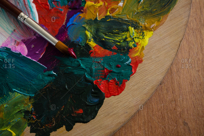 Cropped image of paintbrush on color palette at table in art class