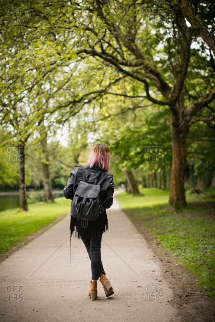Rear view of woman standing with backpack in park