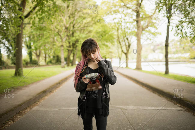 Beautiful woman reviewing photos on vintage camera in park