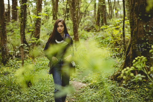 Woman hiking in countryside at forest