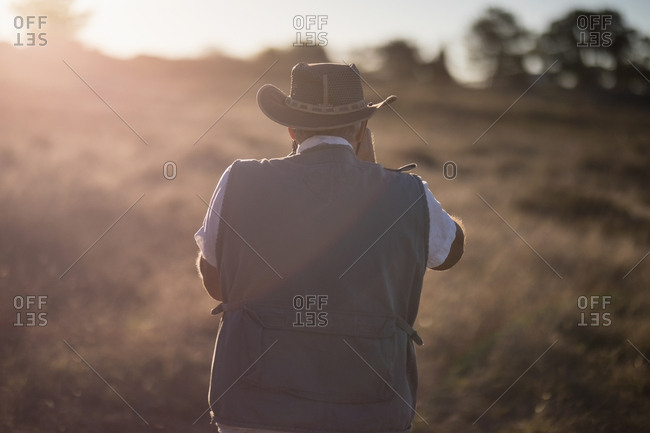 Rear view of man taking picture during safari vacation on a sunny day