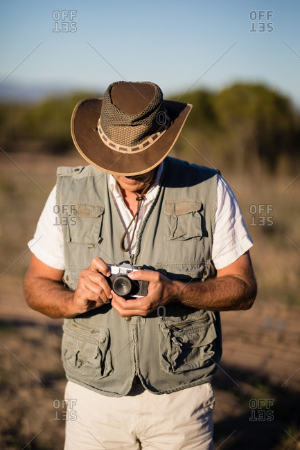 Man adjusting the lens of camera  during safari vacation on a sunny day