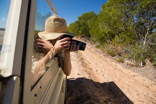 Woman photographing while traveling in vehicle on field