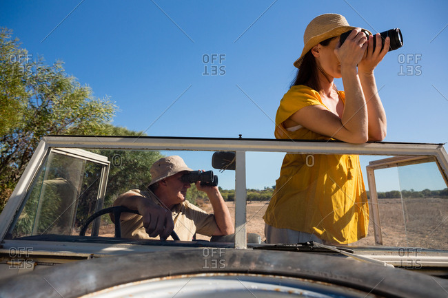 Woman with man in off road vehicle photographing from camera