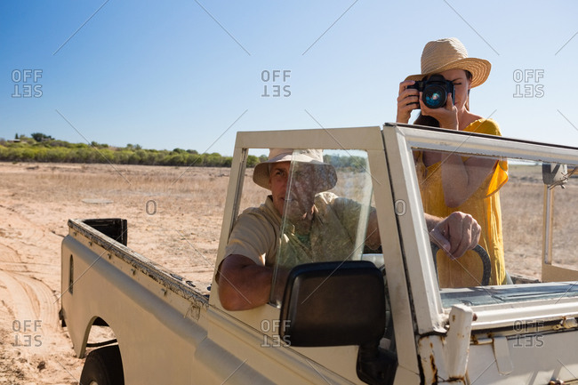 Woman with man photographing while traveling in vehicle on landscape