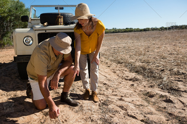 Man with woman digging soil by off road vehicle on field