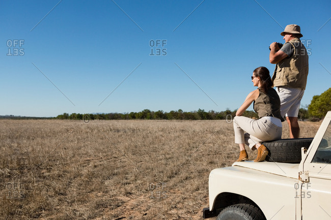 Couple on off road vehicle hood looking at landscape against blue sky