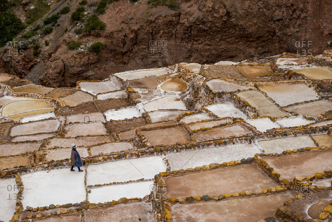 Maras, Cusco, Peru. - May 9, 2017: A person walks through a salt mine consisting of hundreds of salt evaporation ponds.