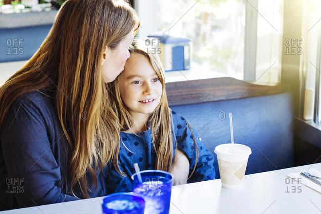 Mature woman with long blond hair kissing daughter while sitting at table in diner