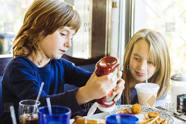 Boy pouring tomato ketchup on plate of French fries for sister in restaurant