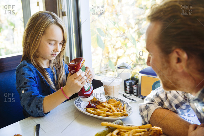 Cute girl pouring ketchup on French fries plate while sitting with father in restaurant