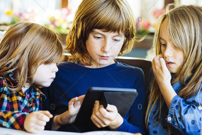 Brothers and sister with long blond hair using digital tablet together in restaurant