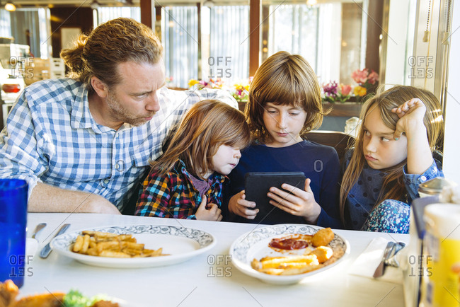 Angry daughter looking at father by siblings using digital tablet at table in restaurant