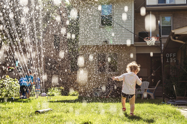 Child running through water spray from the sprinkler