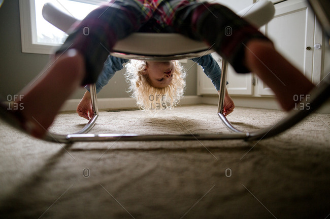 Boy lying across a stool