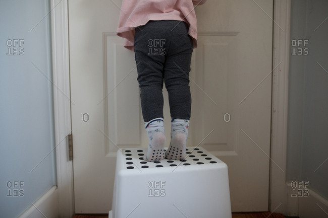 Girl on laundry basket by door