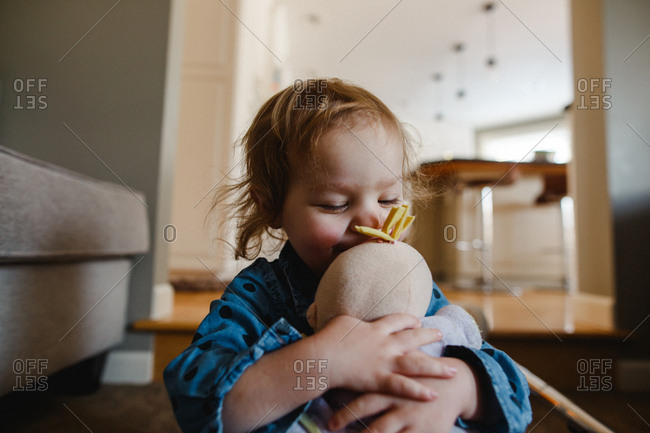 Toddler girl hugging her doll