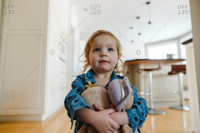 Toddler girl holding onto her doll