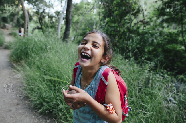 Portrait of girl laughing while standing in forest