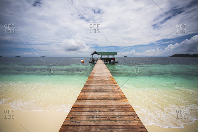 Scenic view of pier at Raja Ampat Islands against cloudy sky