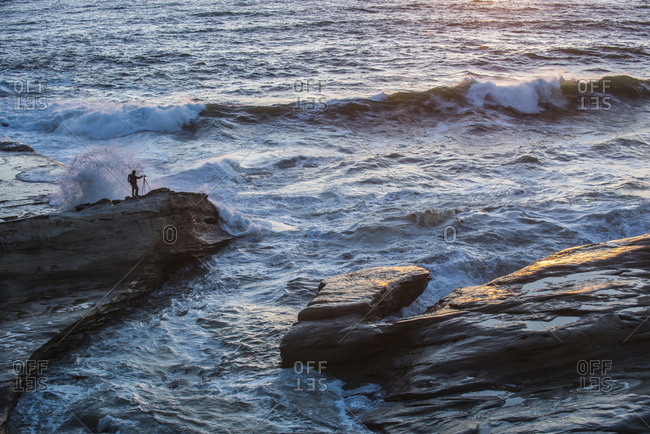 High angle view of person standing on rocks by sea at Cape Kiwanda State Park