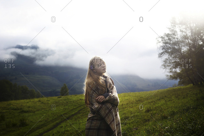 Woman wrapped in a blanket standing on field