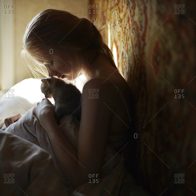 Side view of woman sitting with cat on bed
