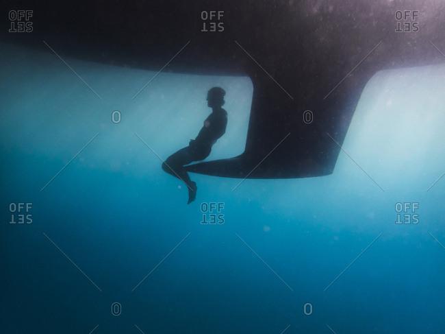 Silhouette man sitting on keel undersea