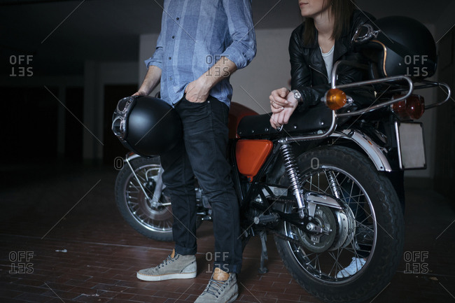 Low section of young couple standing by motorcycle at auto repair shop