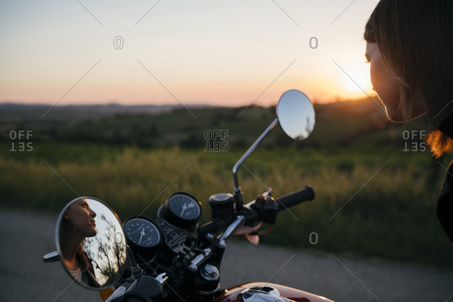 Thoughtful female biker looking away while sitting on motorcycle