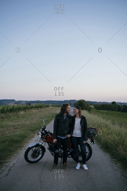 Young couple standing face to face by motorcycle against clear sky at country road