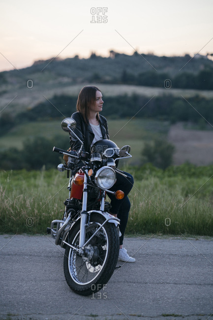 Thoughtful female biker sitting on motorcycle against landscape