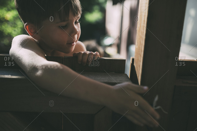 Young boy unlocking a wooden gate from the outside