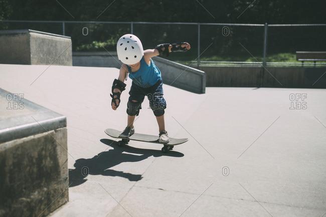 Full length of boy skateboarding at skateboard park during summer