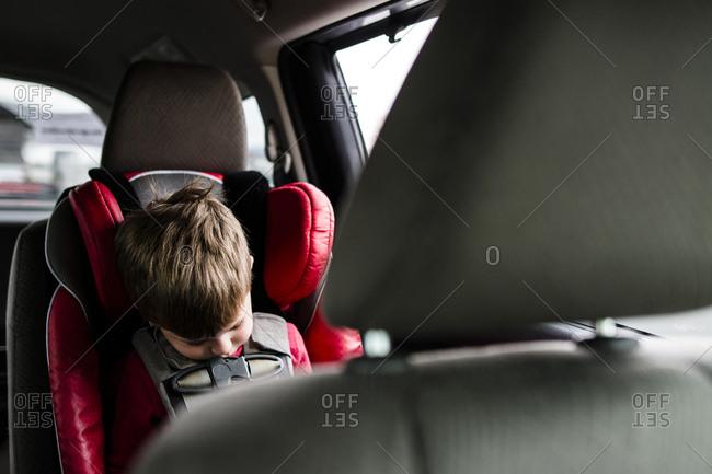 Boy sleeping while sitting in car