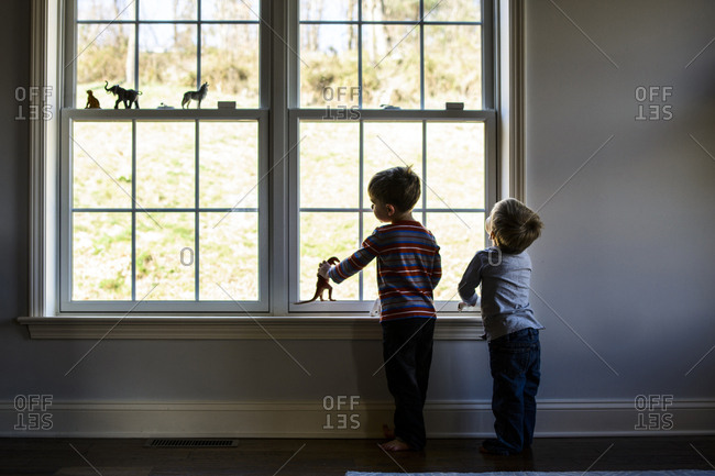 Full length of brothers playing with toys while standing by window