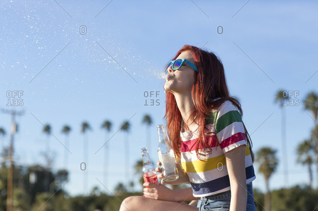Redheaded young woman spitting soda in the air