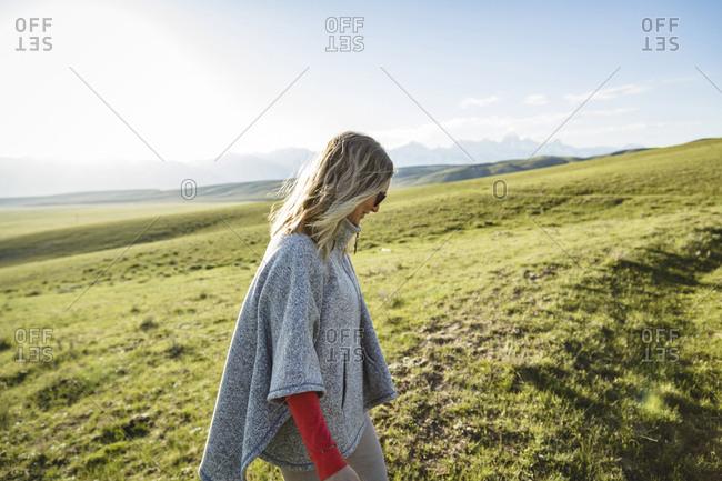 Side view of woman walking on grassy field against sky