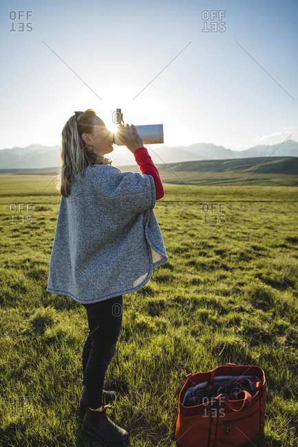 Side view of female hiker drinking water while standing on grassy field against clear sky