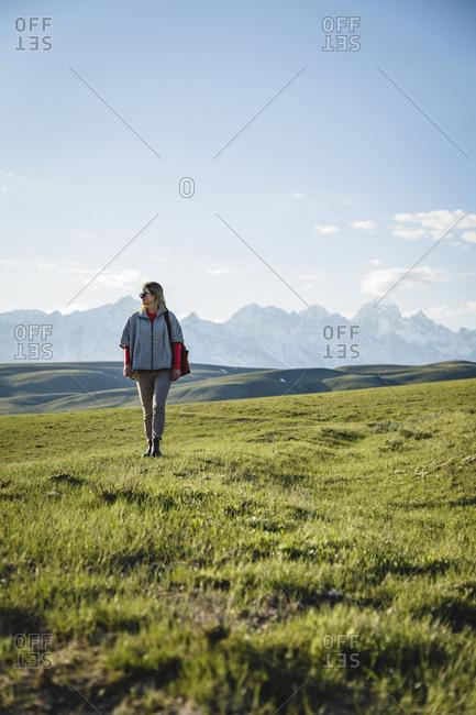 Full length of woman walking on grassy field against sky