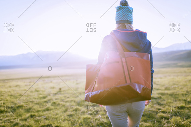 Rear view of female hiker with bag walking on grassy field