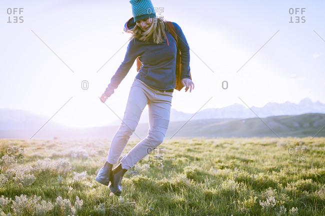 Female hiker jumping on grassy field against sky