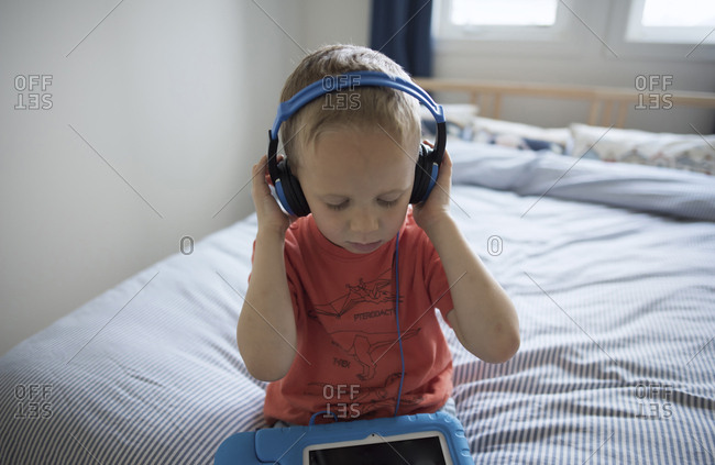 High angle view of boy listening music while sitting on bed at home