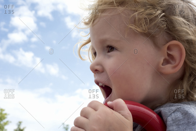 Close-up of cute girl shouting at playground against sky