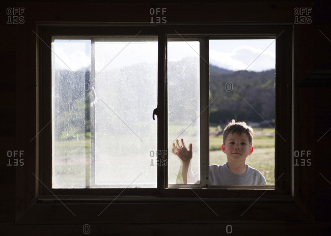 Boy looking into window of dark room from outside