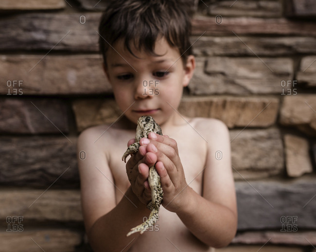 Playful boy holding frog while standing against wall
