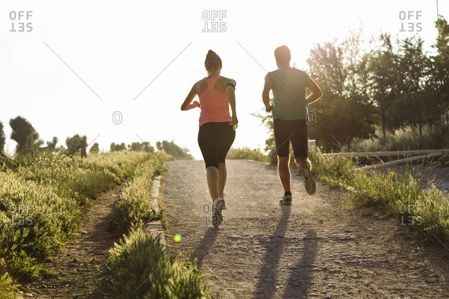 Rear view of young couple jogging on dirt road at park against clear sky during sunset