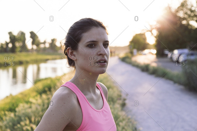 Thoughtful sportswoman looking away while standing against lake at park